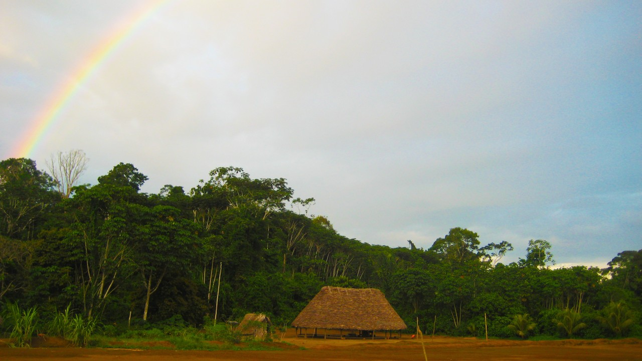 achuar village with rainbow