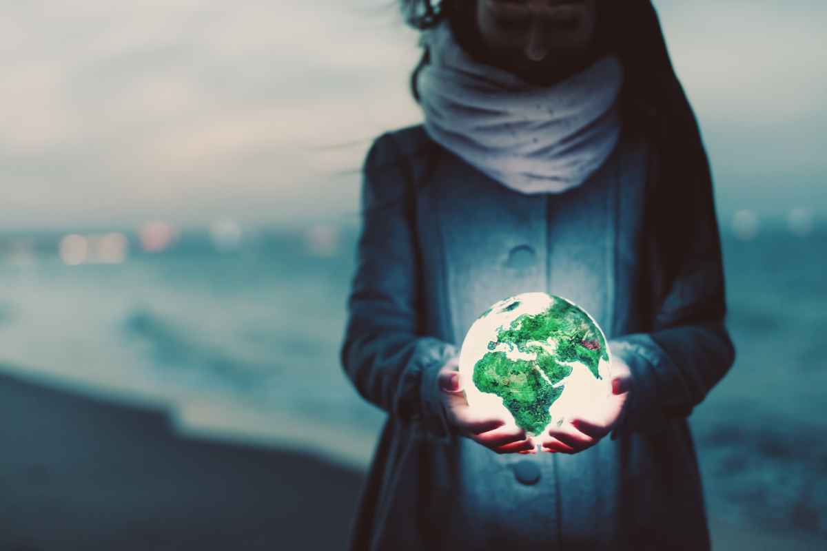 Image of a woman holding the Earth in her hands on a beach for Gondwana Ecotour's post on Earth Day!