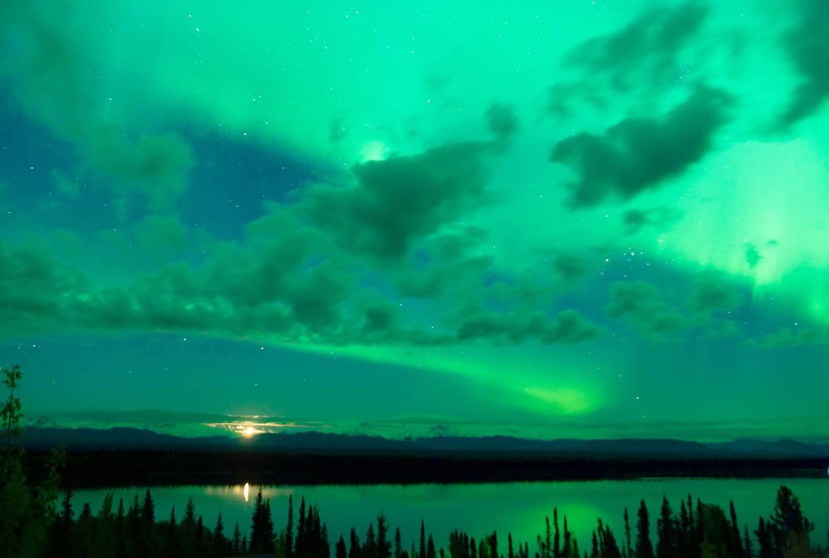The Aurora Borealis peeking through the clouds in Alaska
